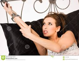 pretty woman angry restrained handcuffs wrought iron bed frame royalty free stock photo