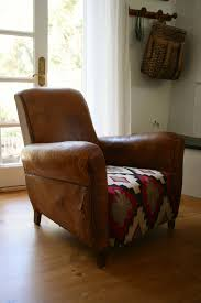 decor brown leather club chair with stripe rug and side table for