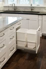 8 ways to hide or dress up an ugly kitchen trash can view in gallery double garbage cans hidden in white cabinetry