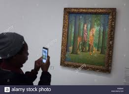 visitor uses his smartphone to photograph the painting le blanc seing the blank signature