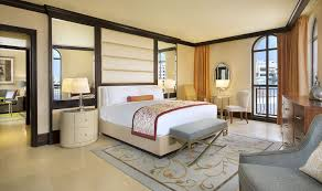 luxury hotel suites abu dhabi the ritz carlton abu dhabi grand suite bedroom decorated in cream and dark wood and featuring a king sized bed with