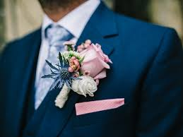 blue boutonniere pink boutonniere with blue and ivory flowers on a navy suit