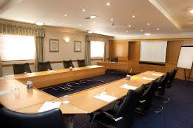 rustic meeting room with rectangular white wooden table and black