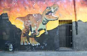 a streetcar a giraffe and a few dinosaurs as i walk toronto part of a mural with a dinosaur