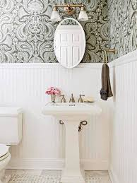 oval medicine cabinet with mirror white beadboard wainscoting in bathroom with wallpaper and pedestal sink and oval medicine cabinet with mirror