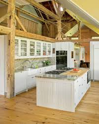 spacious kitchen in a converted barn old house restoration oak flooring gives the space a rustic feel a butcher block surface on the island