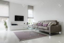 white living room with taupe leather sofa and glass table on