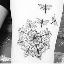 dragonflies form a mandala shape around a flower in this spiritual