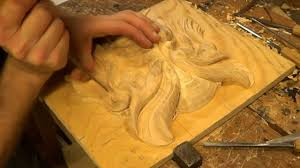 carving a grotesque mask in wood