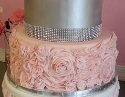 wedding cake extract all tiers covered in fondant ruffled flowers on bottom tier are