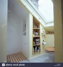 shower and shelves in modern white attic bathroom with wooden