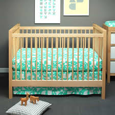 turquoise baby bedding with wooden crib in the baby room