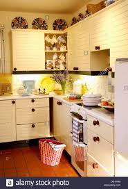Cottage Kitchen by Cream Cottage Kitchen With Red Basket On Terracotta Tiled Floor