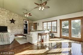 country living room with hardwood floors ceiling fan in