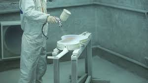 man with a spray gun in his hands paints the white color guitar in