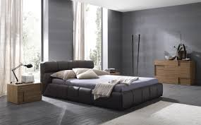 dark grey leather bed with headboard next to brown wooden bedside