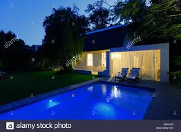 modern house overlooking illuminated swimming pool at night stock