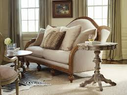 long grey sofa and rustic round accent table near classic armchair