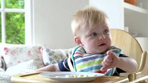 High Chair That Sits On Chair Young Blonde Sits In High Chair In Kitchen Eating Slices Of