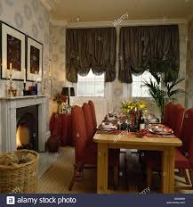 diningroom with festoon blinds and table and upholstered red