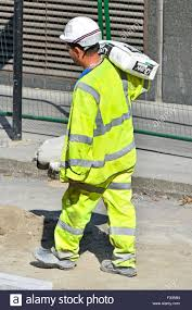 Construction High Visibility Clothing Labourer Carrying A Bag Of Cement On His Shoulder Wearing High