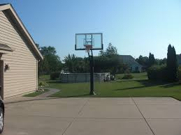 an above ground pool sits well behind a backyard basketball court