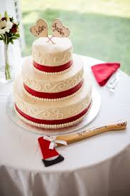 ivory wedding cake with red ribbon