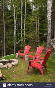 cottage style backyards red plastic garden chairs around rock fire pit in backyard of