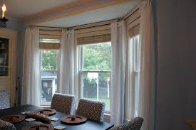 grey bay window curtains on the white wall with white table lamp