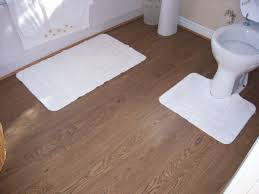 toilet white bathroommat wooden laminate flooring cream color of