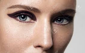 closeup of women u0027s eyes with bright cat eye makeup stock photo