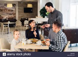 friendly smiling waiter taking order at table of family