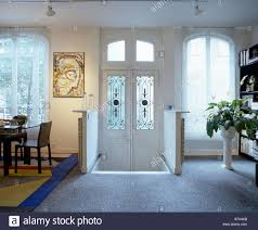 half glazed white double doors and grey carpet in traditional half glazed white double doors and grey carpet in traditional white hall dining room with ceiling spotlights
