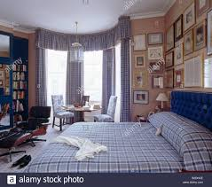blue checked bedlinen and matching curtains in traditional pink