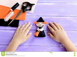 child shows a halloween witch doll child put his hands on a