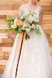 purple and orange wedding dress holds wildflower wedding bouquet pink orange white