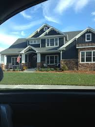 love the dark blue siding dark brown brick and white pillars trim