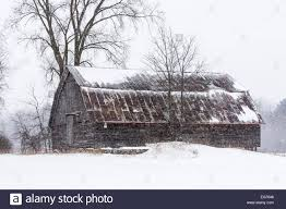 snow falling around weathered barn with rusted metal gambrel roof