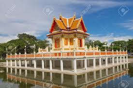 a thai style pavilion at center of pool it has a buddha statue