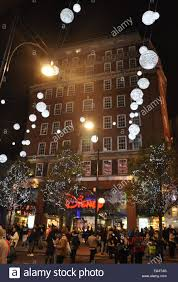 shoppers outside oxford street disney store with christmas lights