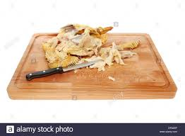leftover chicken carcass stripped meat and a kitchen knife on a