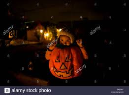 mexico city halloween a boy wearing a halloween pumpkin costume sits near a tomb at the