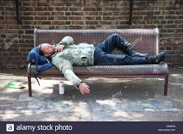man possibly homeless street drinker sleeping on a bench in