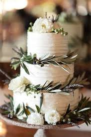 three tiered wedding cake with olive branches decorating it
