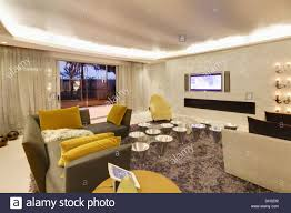 yellow velvet cushions on gray sofas in large modern spanish