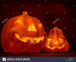 scary glowing pumpkin with creepy spiders on dark red background
