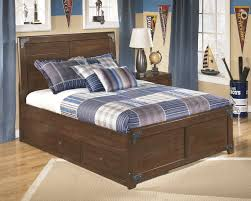 brown bed frame with storage drawers underneath and