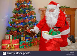 santa claus or father christmas putting presents under the tree