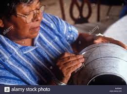 native american woman painting decoration on ceramic pot hand