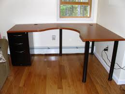 l shaped brown wooden desk with black wooden bases and drawers on